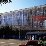 Фотофакт: недостроенный корпус «Волны» закрывают гигантской рекламой